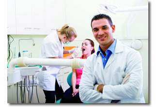 Dentist smiling with patient in the background getting their teeth checked out.